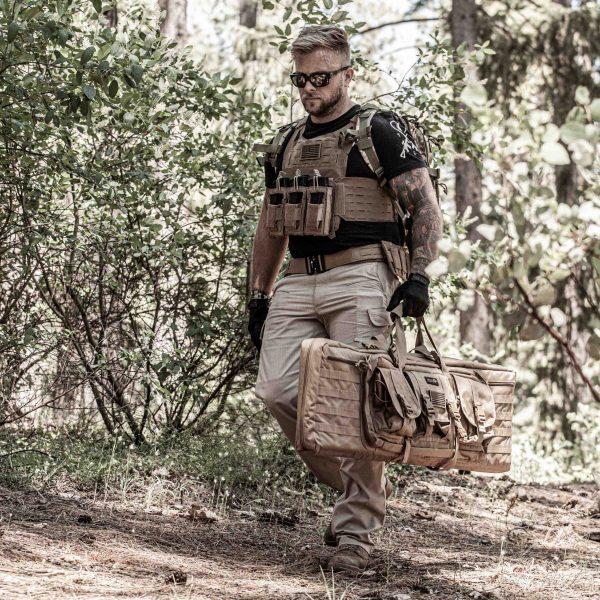 Adult male in woods wearing tan BattleVest Lite lightweight plate carrier vest with K3 Battle Pouch
