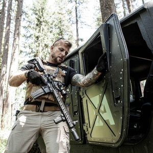 Adult male in woods wearing FDE Tan BattleVest Plate carrier in front of Hummer
